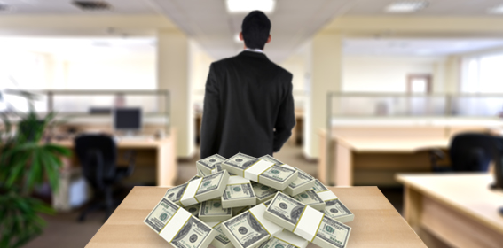 Image of a man walking away from a table with stacks of money on it