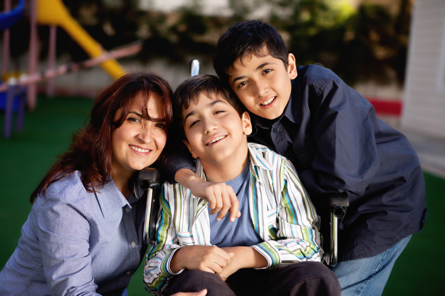 A young boy in a wheelchair with his brother and mother