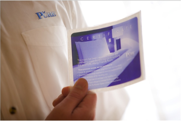 image of a hand holding a PURE certification card