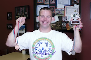 Tim poses with his medals from the 2012 Special Olympics