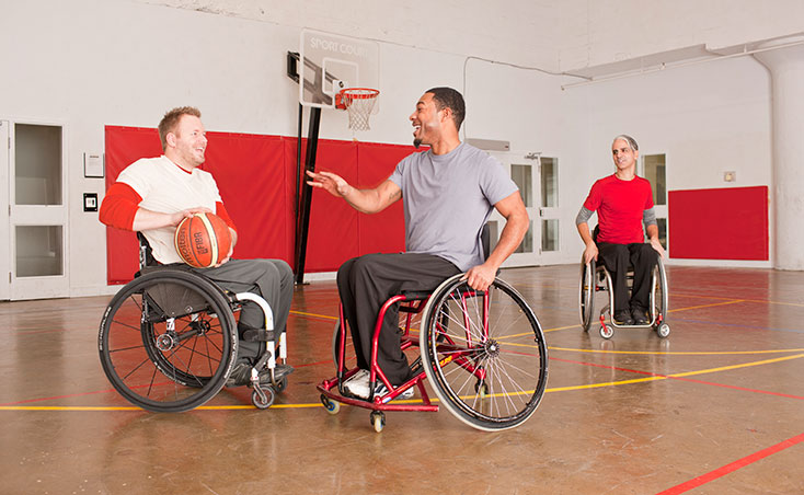 3 men in wheel chairs playing basketball wearing IZ Adaptive designs