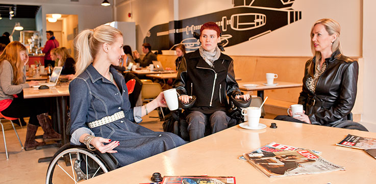 3 women in wheel chairs sitting around a table conversing wearing IZ Adaptive designs