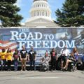 Many people, some in wheelchairs, standing in front of the ADA Legacy Bus