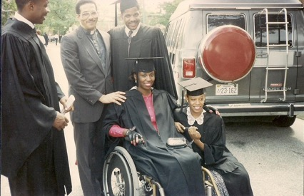 Carmen Jones, in her wheelchair and cap-and-gown, surrounded by 4 people