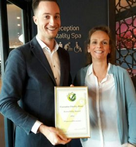 A man holds an award, standing next to ATO founder Marlies van Sint Annaland