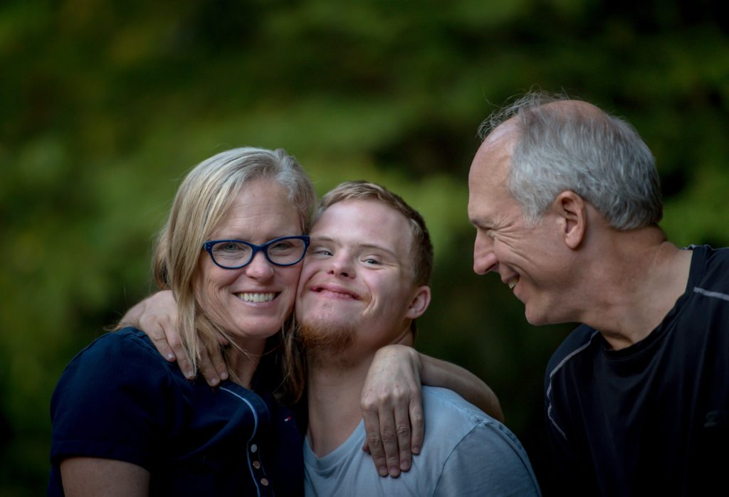 A young man with Down syndrome hugs his mother and father.
