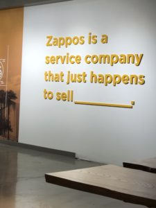 A wall at the Zappos office reads 'Zappos is a service company that just happens to sell _______.'