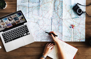 photo of a person planning a trip using a laptop and a map